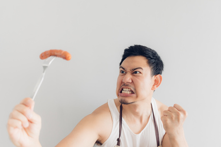 Asian man is angry on the sausage as it is not what he expected for his diet or not delicious.