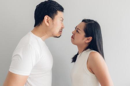 Amante de la pareja asiática enojado en camiseta blanca y fondo gris.