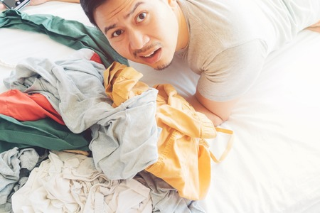 Shocked and sad Asian man who has to take care of all the pile of clothes. Reklamní fotografie