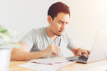 Upset and serious Asian man has problems with billing and debts.