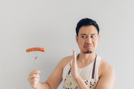 Hate face of Asian man denied to eat sausage. Concept of hate and diet.