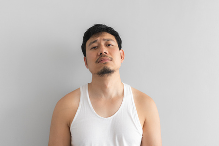 Poor and depressed Asian man wear white tank top on grey background. Concept of desperate life. Stock Photo
