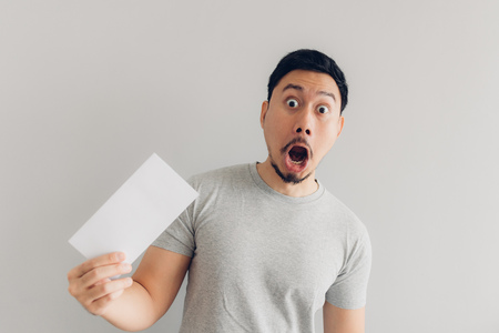 Asian man is shocked and surprised with the white mail message or the bill. Stock Photo