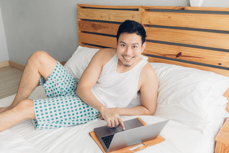 Happy Asian man is working with his laptop on his bed. Concept of freelancer successful lifestyle. Reklamní fotografie