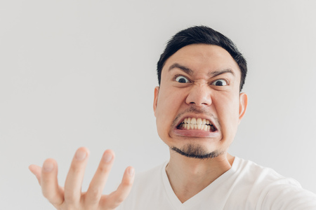 Close up face of angry Asian man selfie himself.