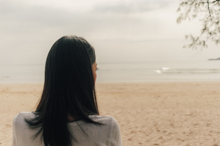 Lonely Asian woman stand on the beach and look into the sea.