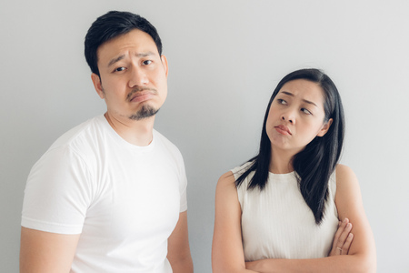 Sad Asian couple lover in white t-shirt and grey background.