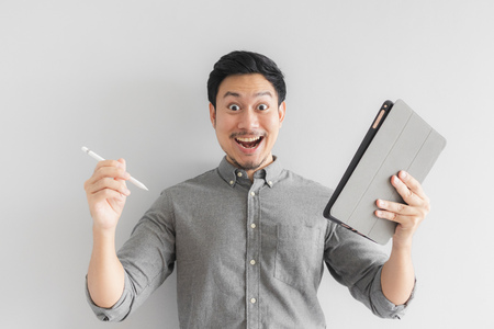 Wow and surprised Asian entrepreneur businessman work on his tablet with grey background. Фото со стока