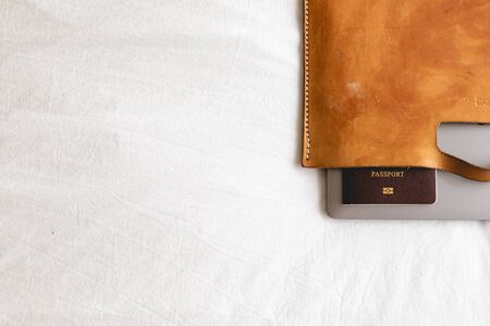 Minimal composition of leather suitcase with passport and laptop in concept of travel business.