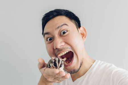 Happy Asian man is taking selfie of himself and his Sugar Glider pet.