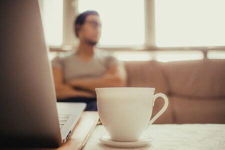 Cerca de la taza blanca de café caliente sobre la mesa de un hombre independiente. Foto de archivo