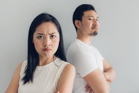 Angry Asian couple lover in white t-shirt and grey background.