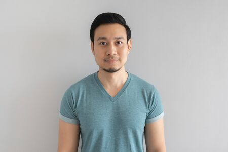 Normal straight face portrait of Asian man in blue t-shirt on grey background.