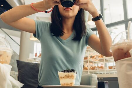 Asian woman is taking a photo of her blueberry cheesecake. Stock Photo
