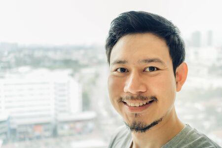 Glücklicher asiatischer Mann selfie in seinem Eigentumswohnungsraum.