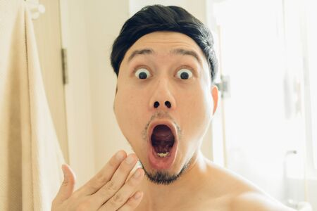Shocked face of an Asian man in the bathroom.