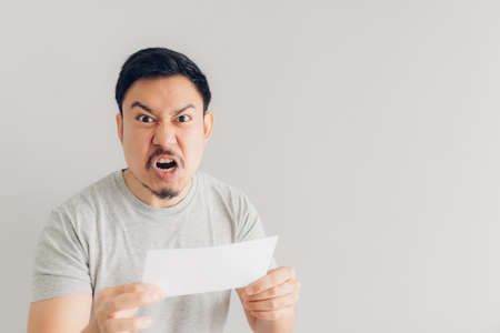 Asian man is angry with the white mail message or the bill.