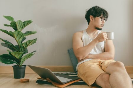 Asian man is working in his living room of his apartment in concept of work from home.
