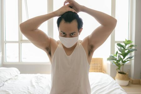 Long hair Asian man with hygienic mask is bored of being quarantine.