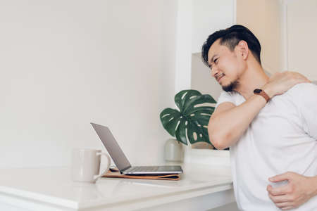 Asian man feels tired from working with laptop in his apartment.