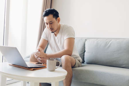 Serious Asian man is working on his laptop in the living room. 免版税图像