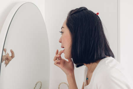 Asian woman is checking her lips on the mirror in white room.