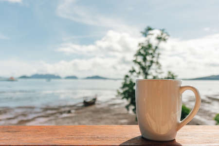 Morning coffee mug with low tide sea view as background.
