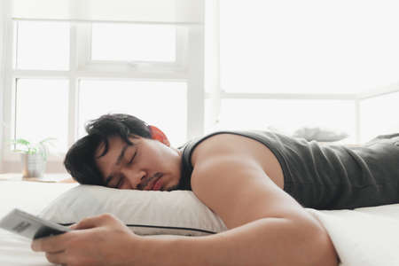 Sleepy Asian man is using smartphone while lying on the bed.