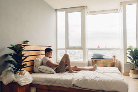 Lonely and depressed Asian man in his bedroom in the apartment. Banque d'images