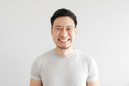 Smile face of happy Asian man wear grey t-shirt and on grey background.