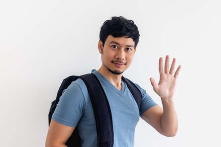 Asian man in blue t-shirt with backpack is waving hand on isolated background.
