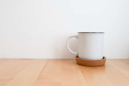 White hot coffee cup on wooden table and white wall with copy space. Archivio Fotografico
