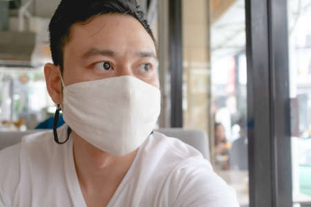 Asian man wears white mask for Covid virus protection in public cafe.