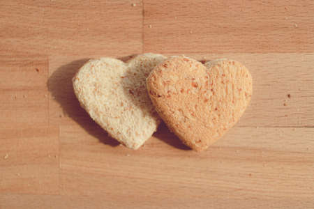Grained bread cut off as heart shape. Concept of love and care in Valentine day.