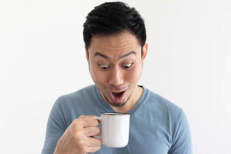 Funny wow face of Asian man in blue t-shirt drinks coffee from white mug. Archivio Fotografico