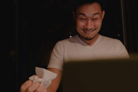 Funny horny face of Asian man watching porn at night.