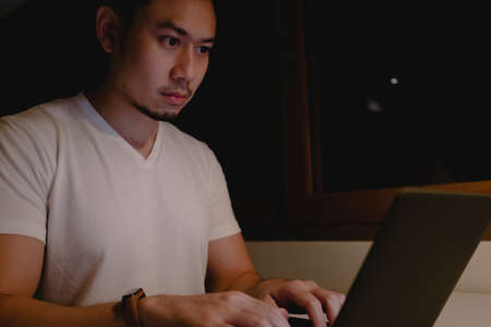 Serious Asian man is working with laptop at night. Concept of work hard and late. Reklamní fotografie