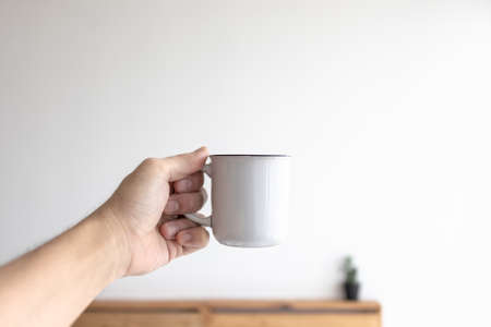 White small mug of coffee in a white cozy room in the morning. Archivio Fotografico
