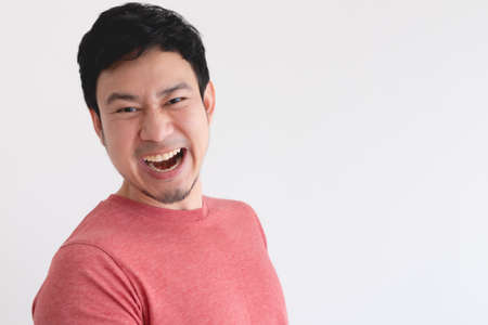 Enjoy and laughing face of Asian man in red t-shirt on isolated background. 写真素材