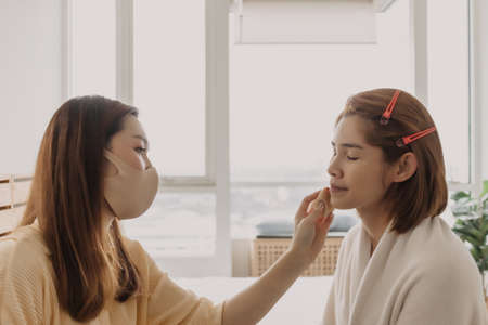 Asian woman makeup artist is at work and wearing makeup on her model.
