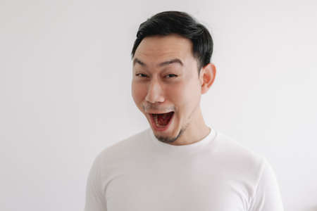 Funny grin smile face of Asian man in white t-shirt isolated on white wall.