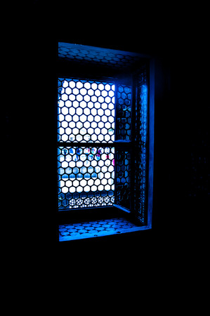 lattice window: Sunlight shining through a lattice window in a dark room. Stock Photo