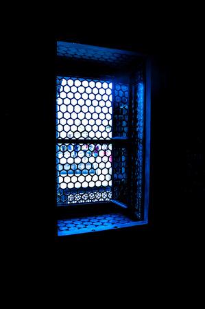 darkroom: Sunlight shining through a lattice window in a dark room. Stock Photo