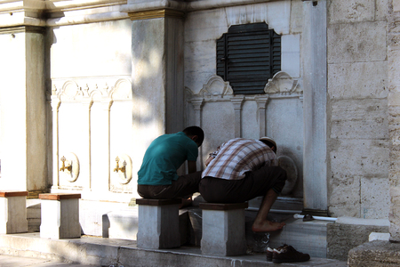 sunni: Istanbul, Turkey - September 15, 2015: People pray at the mosque they ritually washing before.