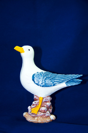 trinket: Trinket seagull isolated on the blue background