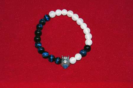 collet: Samurai figure blue and white beads men bracelet isolated on red background