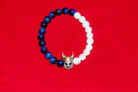 wrist strap: Viking figure blue and white bead men bracelet isolated on red background Stock Photo