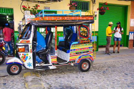mototaxi: Guatape, COLOMBIA - DECEMBER 14, 2016: Colorful mototaxi (tuk tuk) and decorated houses in village Guatape, Colombia