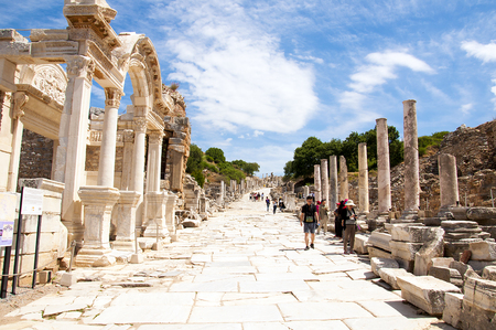 Izmir, Turkey - May 10, 2017: Hadrians temple ruins with tourists walking in anceint city of Ephesus on sunny day