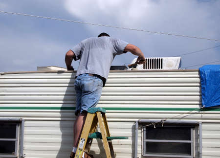 vents: Adult male working on trailer on hot overcast day Stock Photo